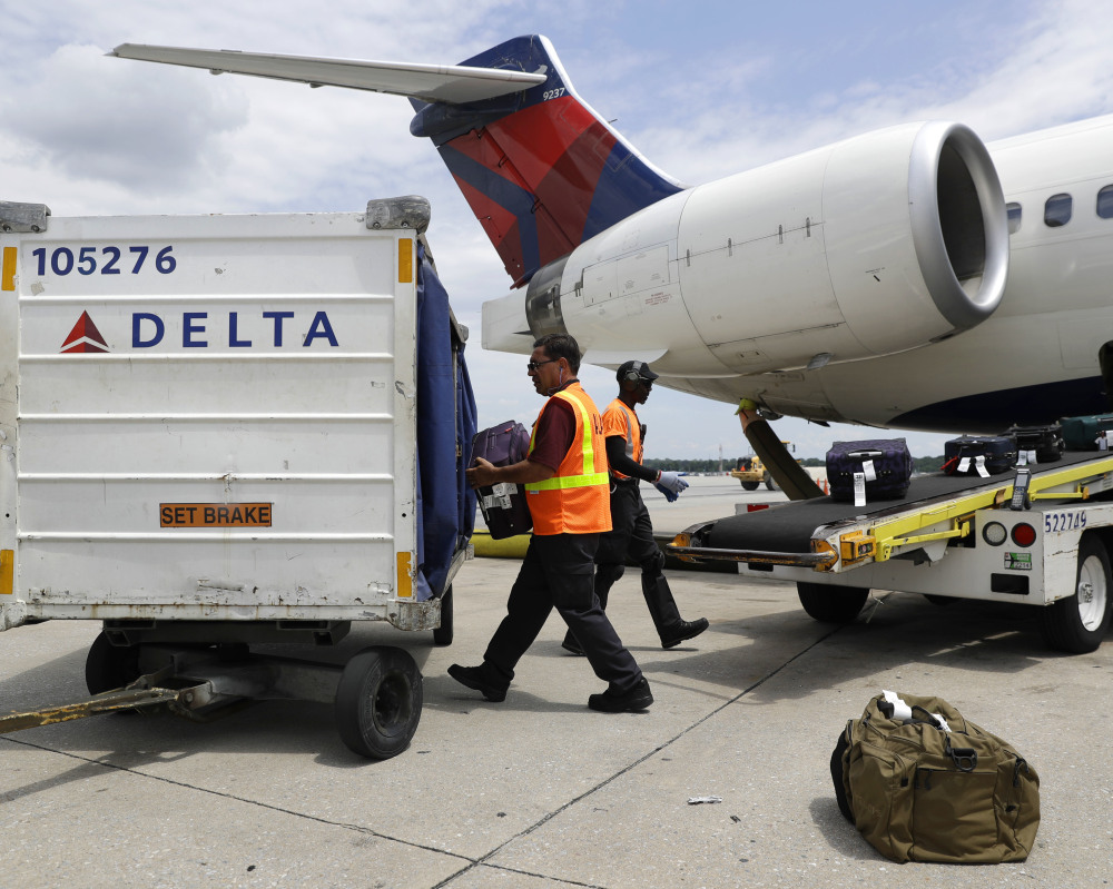 Airport workers unload baggage at Baltimore-Washington International in Linthicum, Md. Delta plans to have its new baggage system online in 344 airports by Sept. 1.