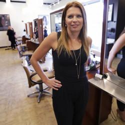 Christine Perkins, who owns Pyara Spa and Salons at two Boston-area locations, poses at her salon in Burlington, Mass. Perkins struggles to find full-time candidates to style hair, do manicures and give massages, in part because some nearby beauty schools have closed.