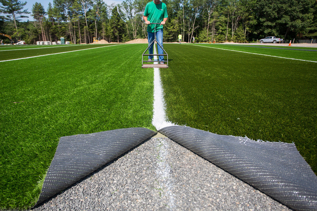 Chris Counts of Northeast Turf, based in Saco, works on the installation of a new turf field at Massabesic High School in Waterboro last month. Fewer than 10 percent of the 153 high schools that are members of the Maine Principals' Association have artificial turf fields.
