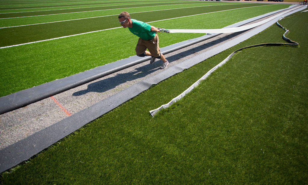 Dylan Rudolph of Northeast Turf, based in Saco, works on the installation of a new turf field at Massabesic High School in Waterboro. Massabesic went with EPDM.