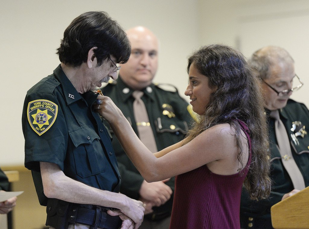 Jon Simonds of North Waterboro has his daughter Kaitlyn pin his new badge on his uniform at the York County Jail on Friday. Simonds, 60, said the job as a corrections officer is the first he's had in a decade that offered benefits. Shawn Patrick Ouellette/Staff Photographer