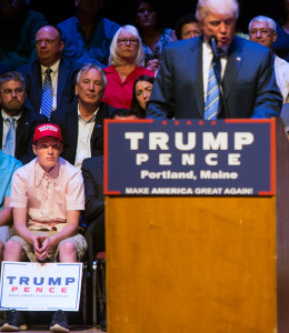 "Connor Mullen, a South Portland High School student who said students and staff members at the school ridiculed him for wearing a ""Make America great again"" hat, got a seat on the stage for Donald Trump's rally in Portland. Derek Davis/Staff Photographer"