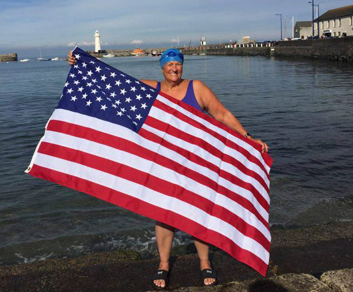 Pat Gallant-Charette holds an American flag on the shore of Donaghadee, Northern Ireland, Thursday to celebrate her crossing of the North Channel of the Irish Sea the previous day. She left from Donaghadee and swam to Scotland. Photo by Tom Charette