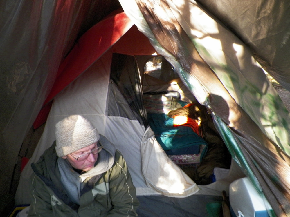 Christopher Knight sits at his camp in April 2013 in the central Maine woods after he led authorities to his campsite.