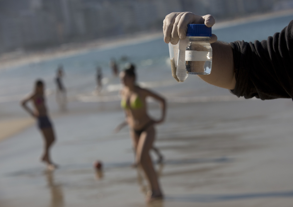 Doctoral candidate Rodrigo Staggemeier shows samples of water and sand from Copacabana Beach in Rio de Janeiro, collected July 11 for a study commissioned by The Associated Press. The 16-month review of the aquatic Olympic and Paralympic venues has revealed consistent and dangerously high levels of illness-causing viruses from sewage pollution.