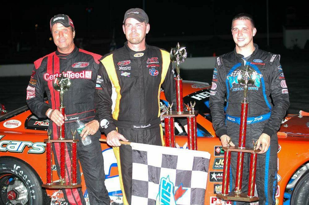 Mike Landry, left, stands with Wayne Helliwell Jr., center, and Joey Polewarczyk on the podium Sunday at Oxford Plains Speedway. Landry finished a career-best third in the H.P. Hood 150.