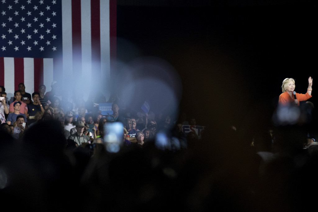 Seddique Mateen (the father of Orlando gay nightclub shooter Omar Mateen), far left at bottom, takes a photo on his phone as Hillary Clinton speaks at a rally at Osceola Heritage Park in Kissimmee, Fla., on Monday.