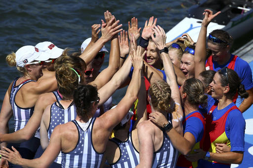 The women's rowing teams from the United States, left, and Romania celebrate on the dock after winning medals in the women's eight event at the Olympics on Saturday in Rio de Janeiro. Romania took the bronze, the United states the gold and Britain the silver.