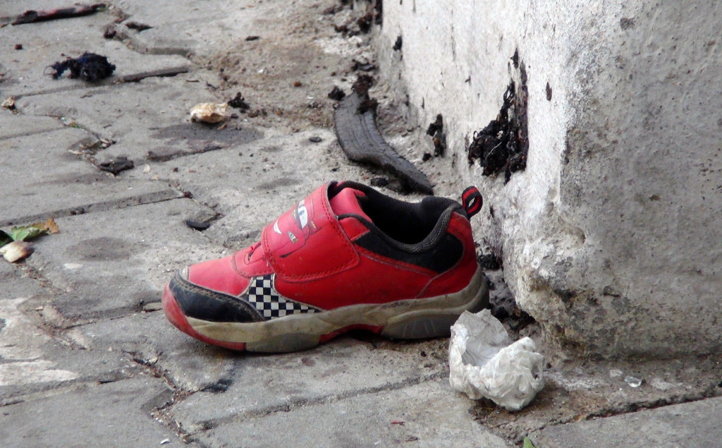 The shoe of a young victim and a piece of metal lie near the scene of Saturday's bomb attack in Gaziantep, southeastern Turkey. IHA via AP