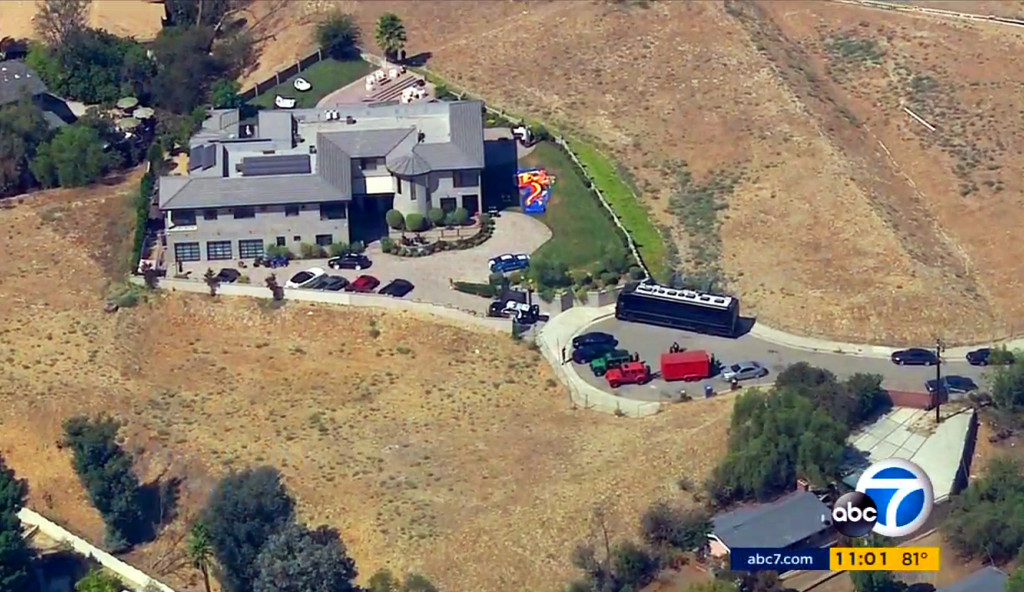 This image from aerial video provided by KABC-TV shows the home of entertainer Chris Brown with a police vehicle outside Tuesday. Authorities waited for a search warrant outside Brown's Los Angeles home Tuesday after a getting a woman's call for help, officials said.   KABC-TV via Associated Press