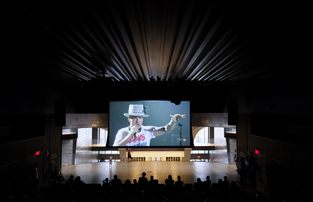 Fans watch The Tragically Hip perform live from Kingston, Ontario, at Studio Bell in the National Music Centre in Calgary, Alberta, on Saturday. (Jeff McIntosh/The Canadian Press via AP)