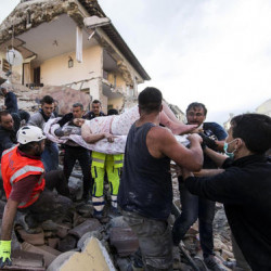 A rescued woman is carried away on a stretcher in Amatrice Italy, Wednesday. Massimo Percossi/ANSA via AP