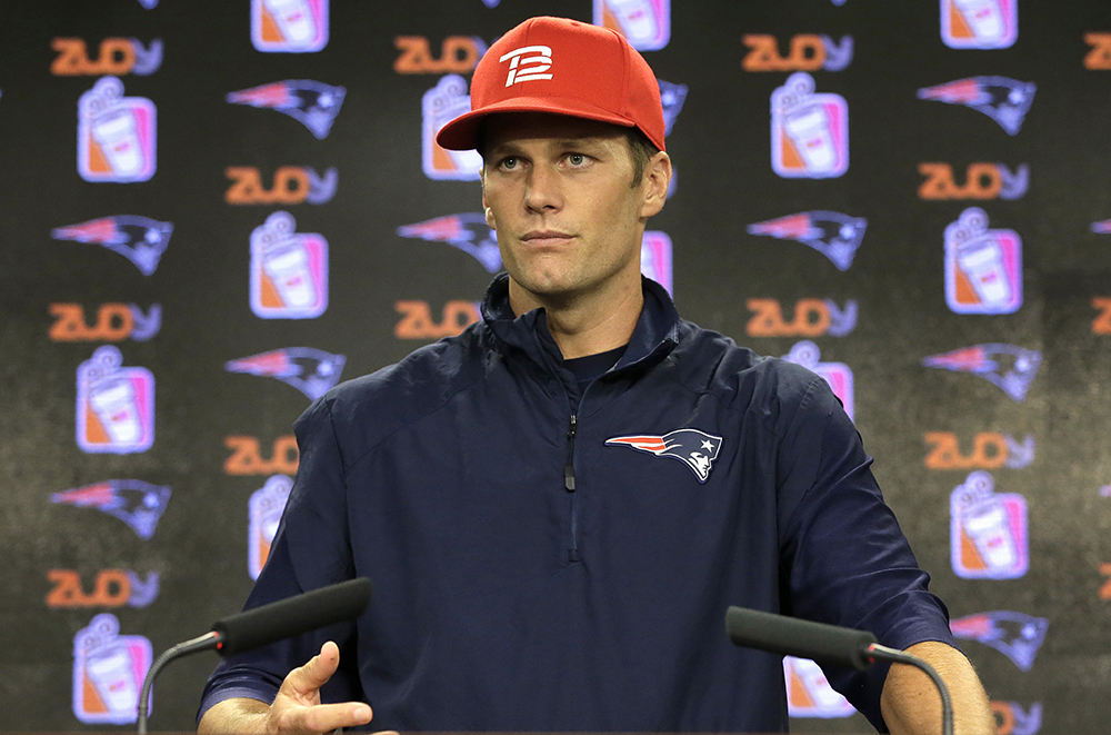 New England Patriots quarterback Tom Brady takes questions from  the news media before training camp practice Tuesday in Foxborough, Mass. He says he's available and ready to play a scheduled preseason game Friday at Carolina. Steven Senne/Associated Press