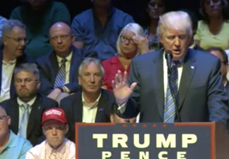"""South Portland's Connor Mullen, wearing his red """"Make America Great Again"""" ballcap behind  Donald Trump at the podium on Thursday, Aug. 4."""