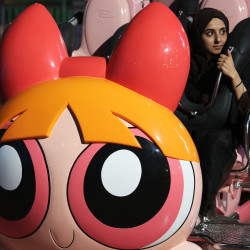 A woman waits for the Powerpuff Girls - Mojo Jojo's Robot Rampage ride to begin at the IMG Worlds of Adventure amusement park in Dubai, United Arab Emirates, on Wednesday.  Associated Press/ Gambrell