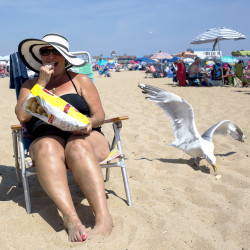 Susan Rancourt, a visitor from Saint-Georges, Quebec, who says she has been summering in Maine for years, soaks up some sun at Old Orchard Beach.  (Briana Soukup/Staff Photographer)