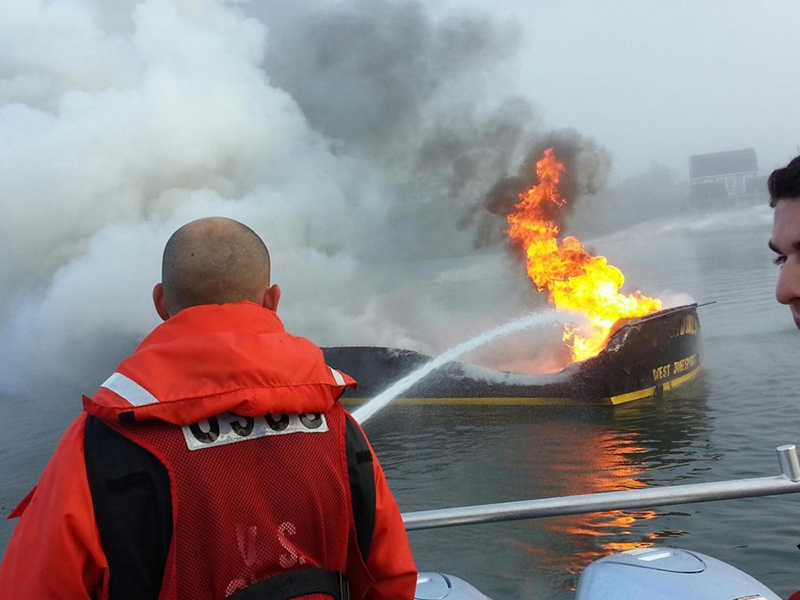 Coast Guard Petty Officer 3rd Class Cory Langston fights the boat fire from the Coast Guard 29-foot response boat.