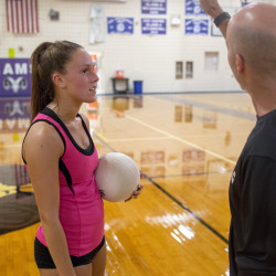 Coach Larry Nichols works with senior Kaylee Helmick during volleyball practice at Deering High. Deering went 7-7 in its first varsity season a year ago and has the potential to become of the premier programs in the state.