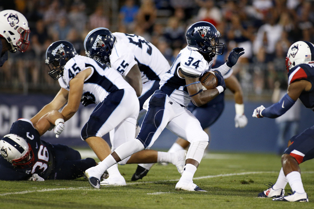 UMaine running back Josh Mack slides past his blockers for first-down yardage during Thursday's college football game at Rentschler Field in East Hartford, Conn.