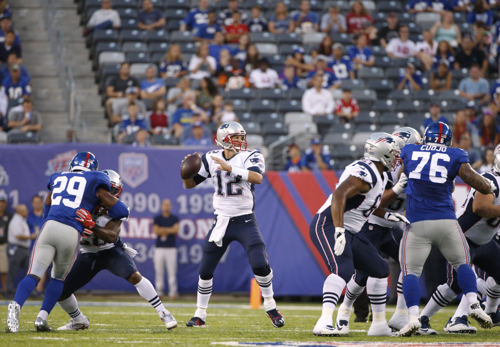 Patriots quarterback Tom Brady looks to pass as New York Giants strong safety Nat Berhe, 29, and Jermelle Cudjo rush during the first half Thursday in East Rutherford, N.J. Brady was intercepted on the play.