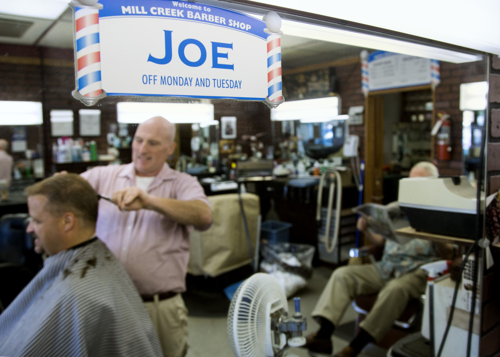 SOUTH PORTLAND, ME - AUGUST 26: South Portland barber Joe Souza, the author of eight horror and crime novels, is reflected in a mirror as he cuts Wade Merritt's hair at Mill Creek barber shop. (Photo by Derek Davis/Staff Photographer)