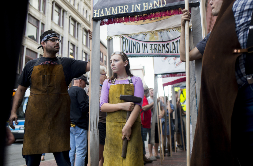 Lucas Damen, left, a part-time blacksmith, and Fuchsia Harmon, 11, who is taking blacksmithing classes, stand with their blacksmith banner before the All Hands On parade, a celebration of working people for Labor Day. The event was inspired by a local history of parading artisan and local banners on Congress Street. Brianna Soukup/Staff Photographer