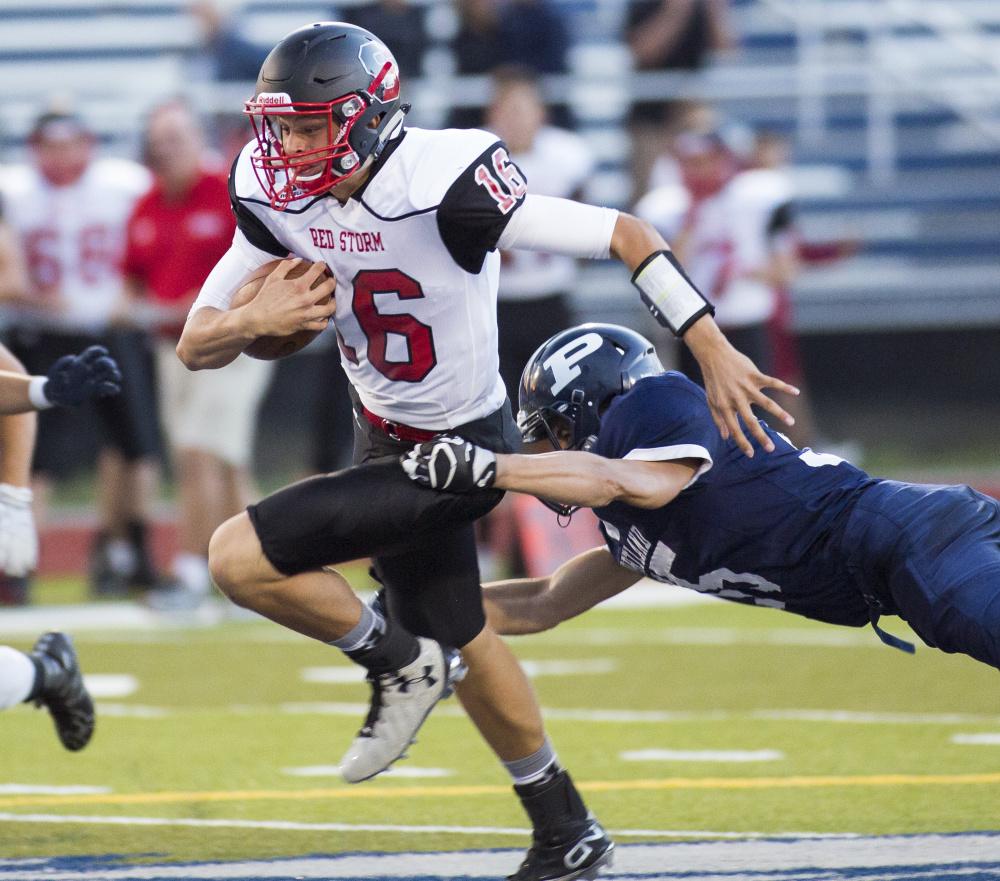Scarborough quarterback Zoltan Panyi runs with the ball in the first quarter of Friday night's opener against Portland High School at Fitzpatrick Stadium. Scarborough won 14-13.