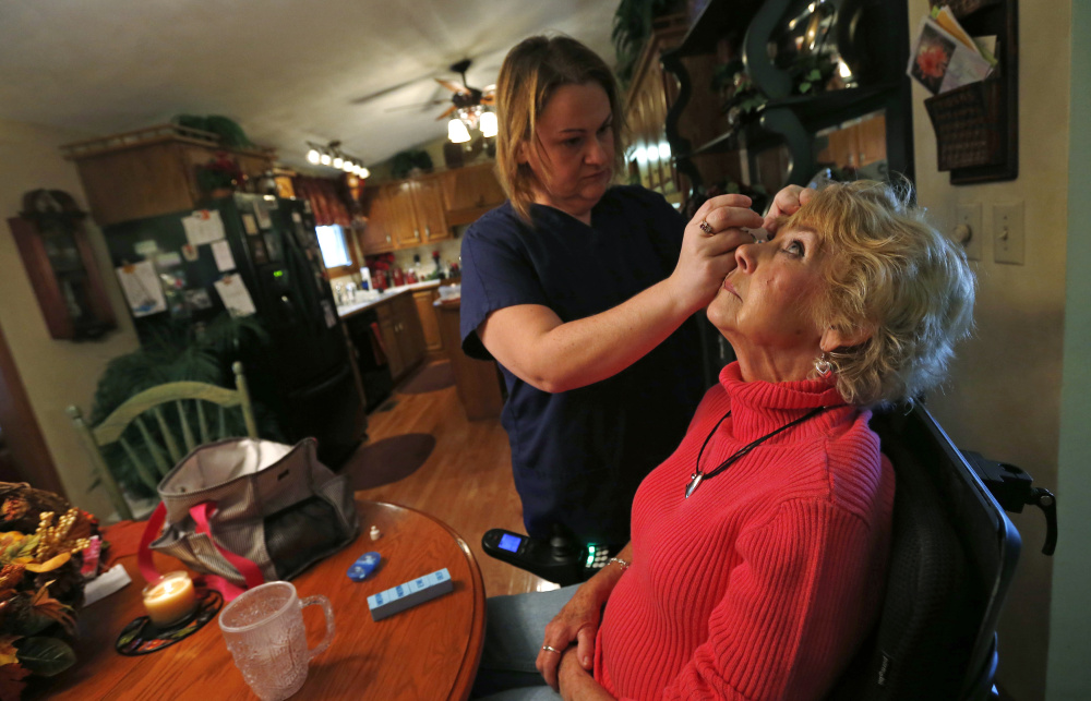 Jessica Haynes, left, a certified nursing assistant, applies eyedrops to Sandy Wright, who has an autoimmune disorder that damages her optic nerve and spinal cord, in Peoria, Ill., in 2013. Though mills and factories created the blue-collar middle class that we celebrate on Labor Day, the jobs that employ the most people today are in service sectors like health care.