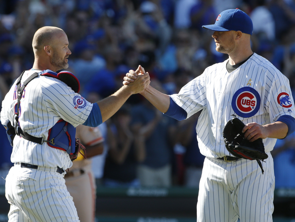 Chicago's Jon Lester, right, celebrates with catcher David Ross after a 2-1 win Friday over San Francisco at Wrigley Field.
