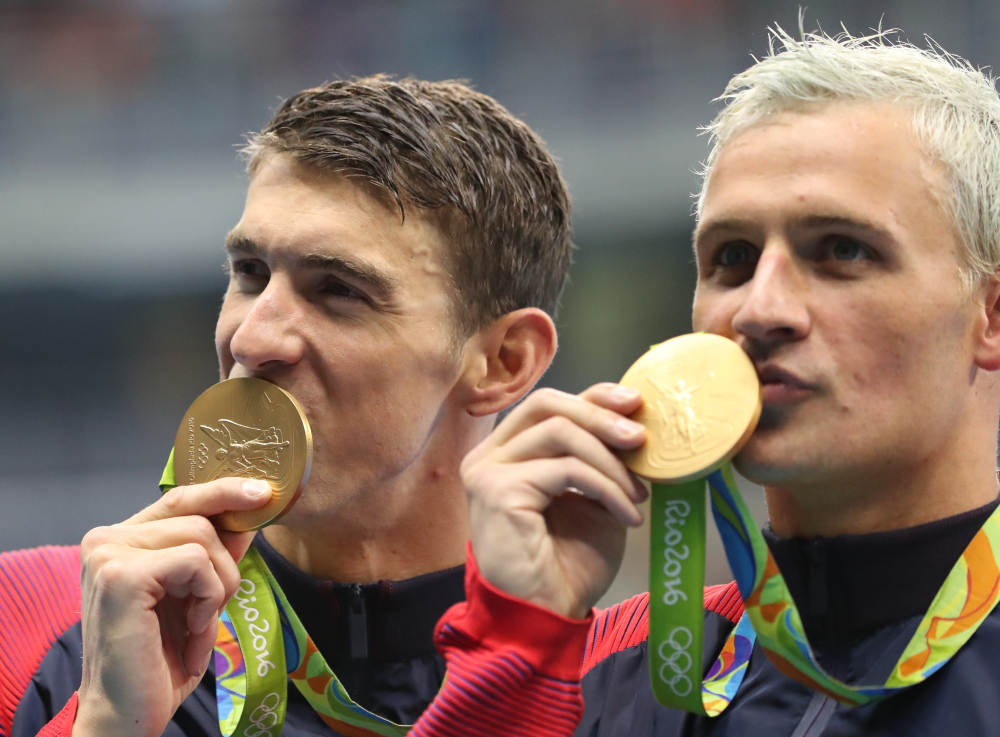 Michael Phelps, left, says he's too busy to show up and root for teammate Ryan Lochte on