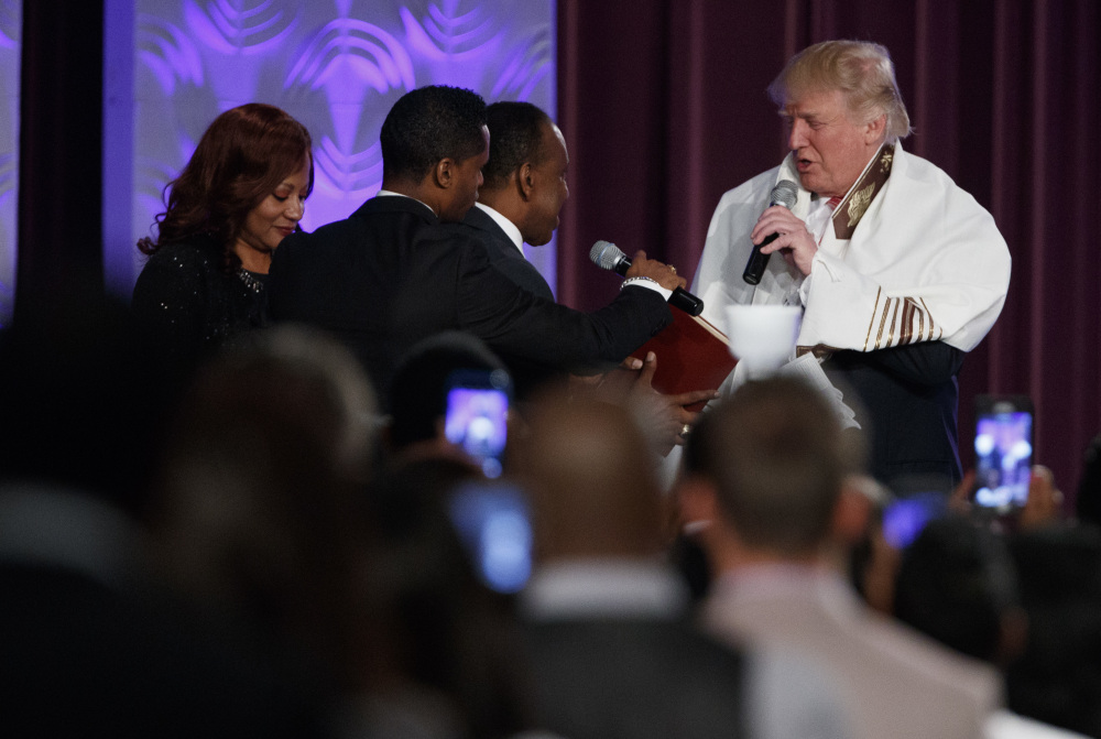 Donald Trump wears a prayer shawl as he is presented with a gift during a service Saturday at Great Faith Ministries International, a predominantly black church in Detroit.