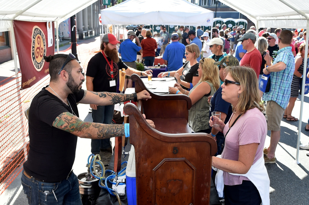 Donna Archambault talks with David Bouchard, head brewer and owner of Crooked Halo Cider, on Saturday at the first Skowhegan Craft Brew Festival.