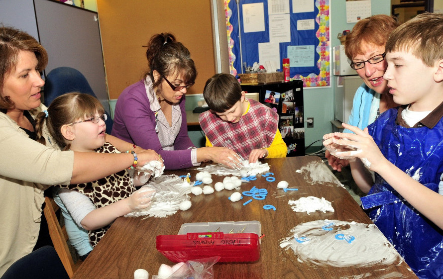 Education technicians work with students on the autism spectrum in a Winslow Elementary School special education class in 2012. From left are Wendy Morrison with Madison Rowe, Anne Rice with Thomas Rowe, and Linda Lemieux with Will Weiss. Turnover in special education is twice the rate of that in other teaching positions.
