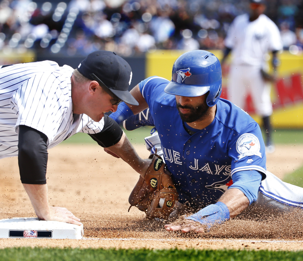 New York third baseman Chase Headley tags out Toronto's Jose Bautista at third during a 5-3 Yankees win over the Blue Jays at New York on Monday.