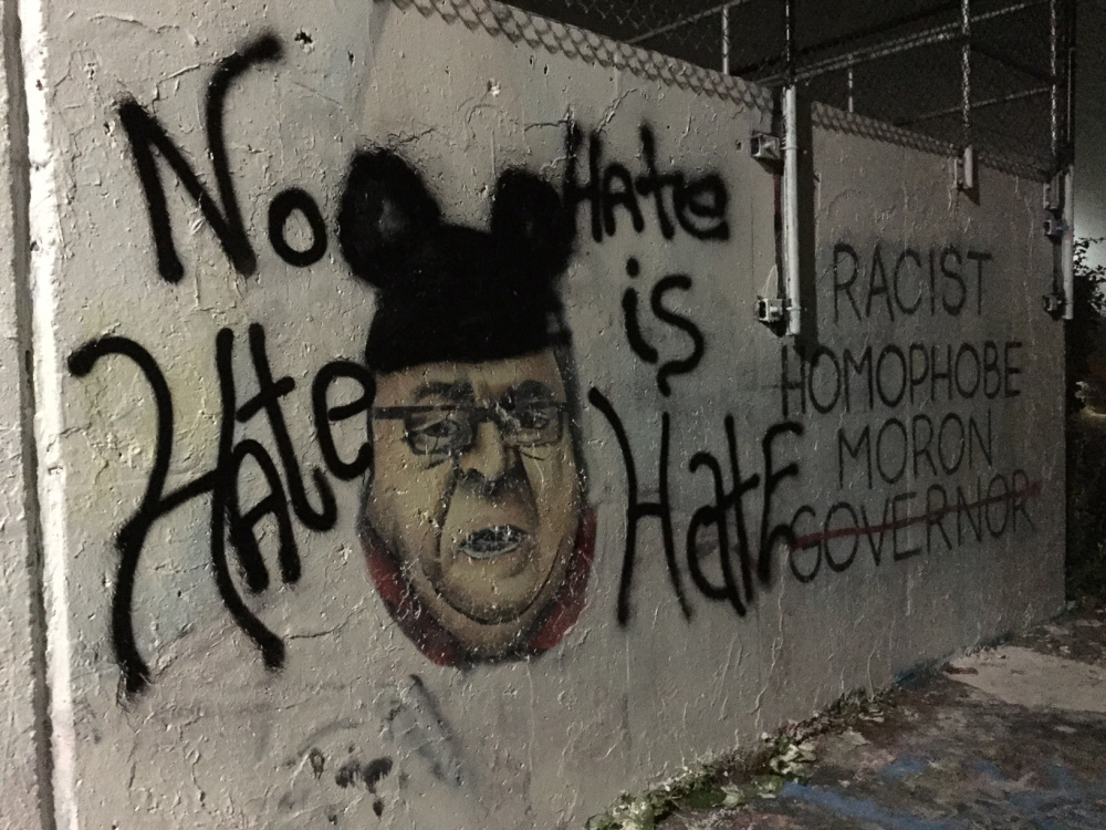 Much of the controversial East End mural had been defaced by competing interests late Tuesday, with the likeness of the governor trading in its KKK regalia for Mickey Mouse ears. Dennis Hoey/Staff Writer
