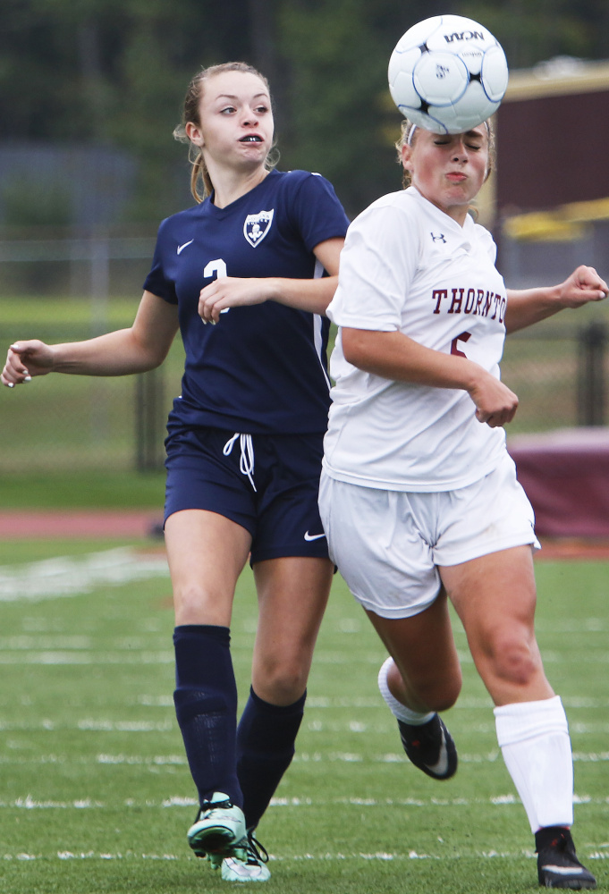 Alyanna Beaudoin of Thornton Academy, right, heads the ball away from Khloe Langella of Westbrook during the second half. Thornton improved to 2-0 and dropped the Blue Blazes to 0-2.