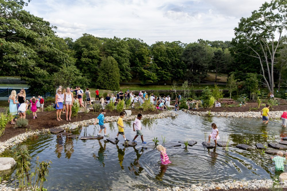 Children use stepping-stones to cross a man-made frog pond in the new Children's Garden at Fort Williams Park on Friday, Sept. 9, 2016.