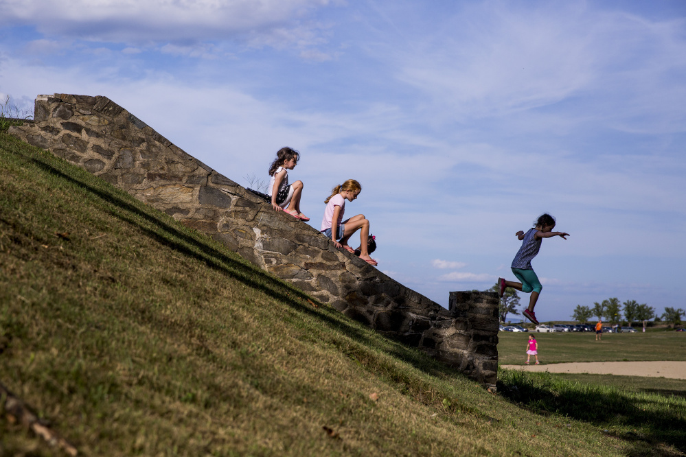 From left, Shyla McVeigh, 7, Hadley Mahoney, 10, and Alexandra Leopold, 7, all of Cape Elizabeth, play at Fort Williams Park in Cape Elizabeth, where 1.5 acres have been transformed into a natural wonderland for children.
