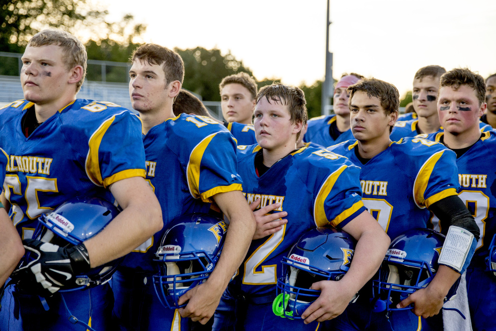 FALMOUTH, ME - SEPTEMBER 9: Shane Allen of Falmouth, center, stands at attention with his teammates as they listen to the national anthem before the start of a high school football game vs. Westbrook September 9, 2016. (Photo by Gabe Souza/Staff Photographer)