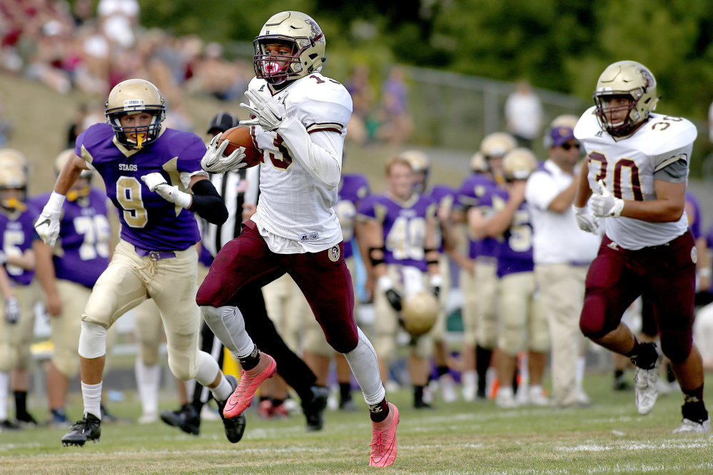 Thornton Academy's Johnny Rosario scampers to the end zone in the first half as Cheverus defensive back Dominic Casale tries to keep up on Saturday. The Trojans cruised to a 65-0 win.