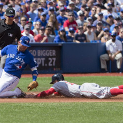 Blue Jays third baseman Josh Donaldson tries to tag Red Sox left fielder Brock Holt as Holt slides safely into third for a stolen base during Boston's 11-8 win Sunday in Toronto.