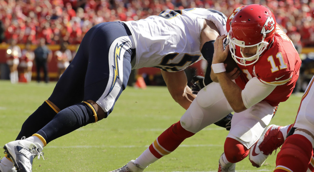 Chiefs quarterback Alex Smith dives past Chargers linebacker Tourek Williams to score the winning touchdown in overtime Sunday. The TD gave Kansas City a 33-27 victory.
