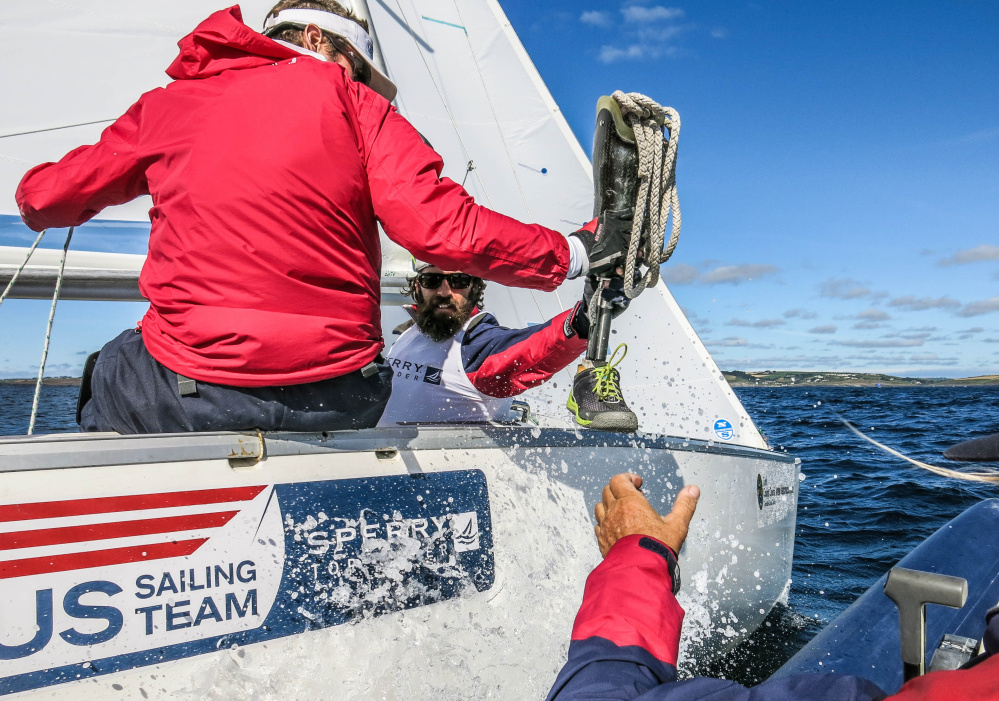 Hugh Freund removes his prosthetic lower leg and hands it to a coach. The prosthesis is not allowed during Paralympic competition. Each of the three sailors in the Sonar class is assessed a point value, depending on the severity of their disabilities.