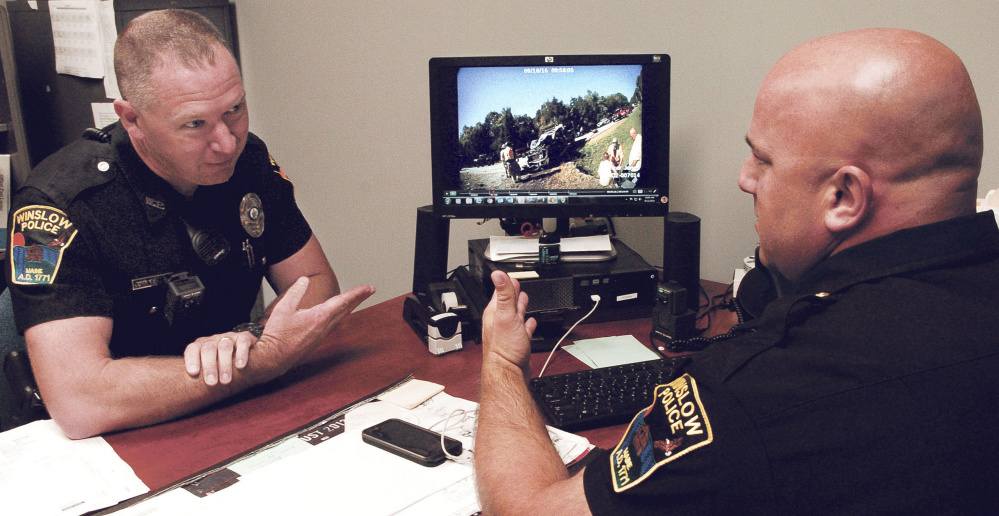 Winslow police officer John Veilleux, left, and Lt. Josh Veilleux discuss a recent car accident while viewing a video taken with a body camera used by an officer.