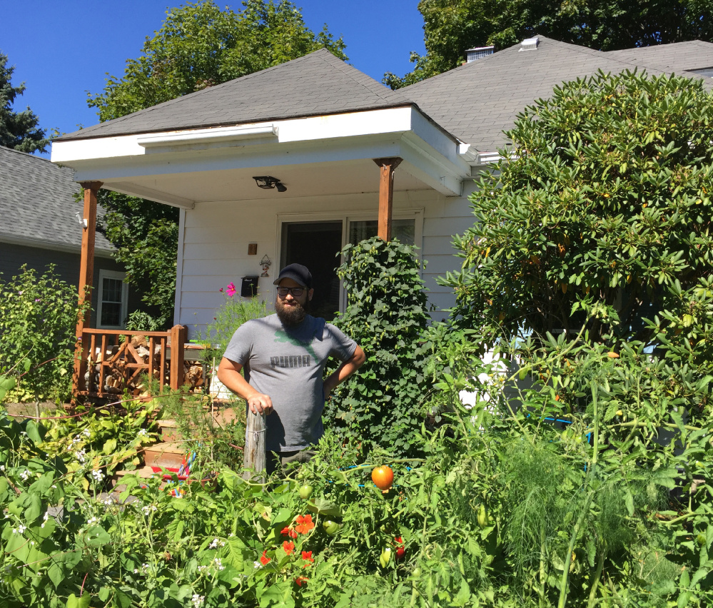 John Hychko of South Portland stands Tuesday in his front-yard garden on Barstow Street, where he and his wife, Shannon, grow a wide variety of vegetables, fruits and flowers without pesticides.