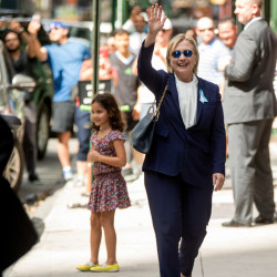 """Democratic presidential candidate Hillary Clinton, seen waving Sunday, left the 9/11 anniversary ceremony in New York early after feeling """"overheated,"""" her campaign said."""