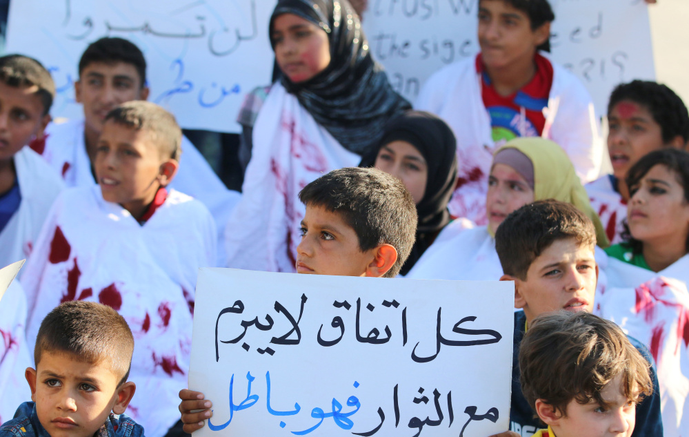 A Syrian boy carries a placard Wednesday during a rally calling for aid to reach the city of Aleppo.
