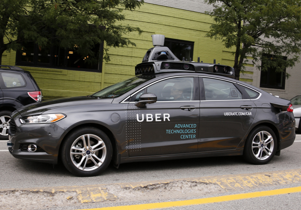 A self-driving Uber car travels through a neighborhood Wednesday in Pittsburgh. About 1,000 Uber customers were offered a free ride in an automated car, each of which had a safety driver and a vehicle operator in the front seats.
