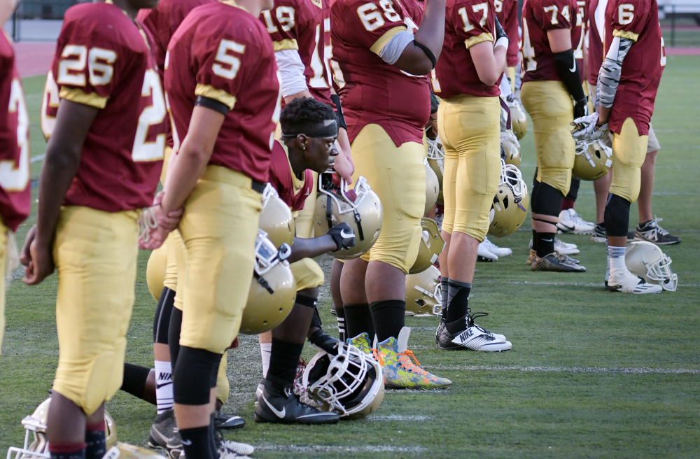 Doherty Memorial High quarterback Michael Oppong kneels during the national anthem before a game in Worcester, Mass., last week. A decision to suspend him was reversed.