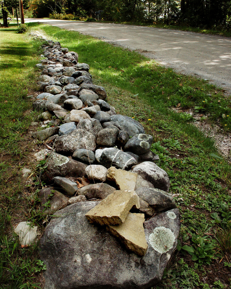 Cinder block pieces used to tether a horse nearby are stacked on a rock wall along Hubbard Road in Canaan.
